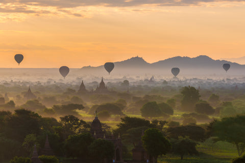 The morning fog rolls in over the temples of the Bagan balloon riders in the morning for sunrise.
