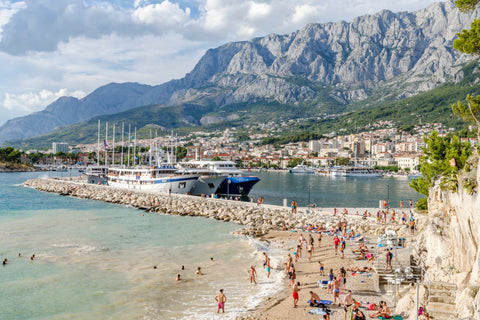Boat dock at Croatian Beach with swimmers and mountains on the coast of Makarska.