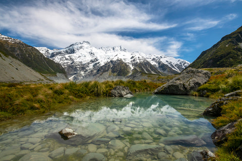 Water reflects the snow capped mountains in Hooker Valley in the south island of New Zealand.