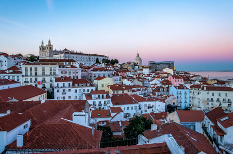 Lisbon at Sunset, pink sky over the red rooftops of the coastal city.