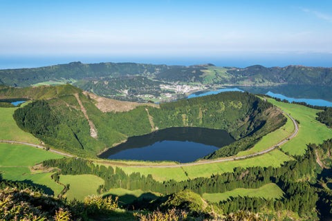 The volcanic formations are in its full form here in Ponta Delgada off the coast of Portugal. Green pine trees line up all around the lake.