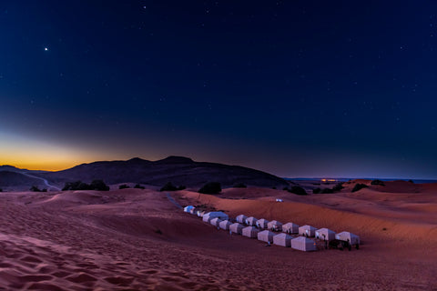 In a tent sleeping under the stars in the Sahara desert with its perfectly clear blue sky.