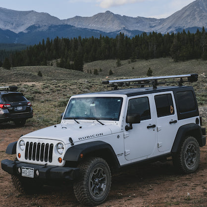 A white Jeep Wrangler with a silver river quiver attached to the top is parked in an open field. In the background is a Subaru Outback also with a silver river quiver mounted to the top, evergreen trees, and jagged mountain tops