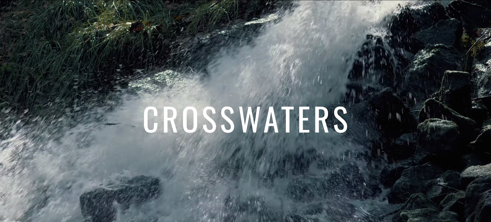 "Image of rushing water over a short water fall. The words ""CROSSWATERS"" is centered on the image in white."
