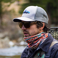 Photo of the side of a man's face in a white hat with a colorful neck tie and fishing gear strapped to his back