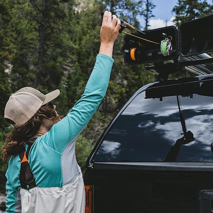 Women wearing fishing waders reaching up to slide a fishing rod into an open fishing pole roof rack. It is mounted to the top of a black pickup truck with a matching black bed cap
