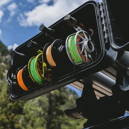 Close up of an open reel box of a river quiver fishing roof rack with 4 reels of varying sizes and colors inside