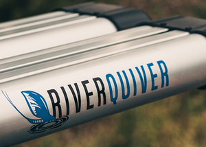 "Close up of the river quiver logo on the side of the silver metal of the 4-banger river quiver's rod casing. The logo says ""river"" in black text and ""quiver"" in blue text with a matching blue image of fishing bait hitting the water. The background is blurred out but looks vaguely like vegetation."