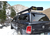 Image of a black pick up truck with a matching black bed cap located in a snowy field with a snowy hill in the background. There is a black 4-banger river quiver with an open reel box mounted to the top of the truck. There are 4 reels of varying sizes inside with varying colors of line.