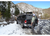 Image of a man sliding a fishing rod into a 4-banger black river quiver. The river quiver is mounted onto a black Chevy pick up truck with a matching black bed cap. The truck is located in a snowy field with a snowy hill in the background.