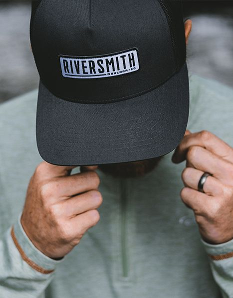 "Man wearing a black trucker hat with Riversmith logo on the front. Logo is a rounded rectangle with a white background and black text saying ""Riversmith, Boulder CO""."