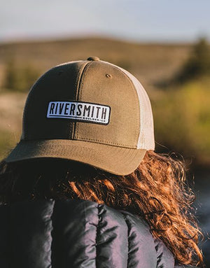 "Women wearing an olive green trucker hat with Riversmith logo on the front. Back of hat is white mesh. Logo is a rounded rectangle with a white background and black text saying ""Riversmith, Boulder CO""."
