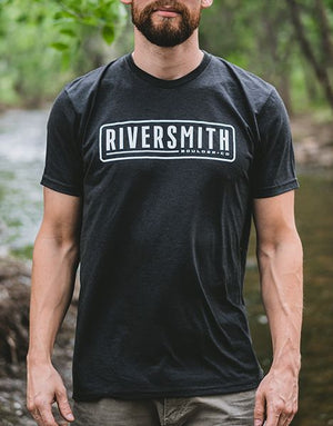 "Man with a beard wearing a black t-shirt that says ""Riversmith, Boulder CO"" on the front in white. Words surrounded by a rounded white box. He is standing by a river with trees."
