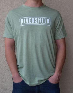 "Man wearing a green t-shirt that says ""Riversmith, Boulder CO"" on the front in white. Words surrounded by a rounded white box. He is standing in front of a textured white wall."