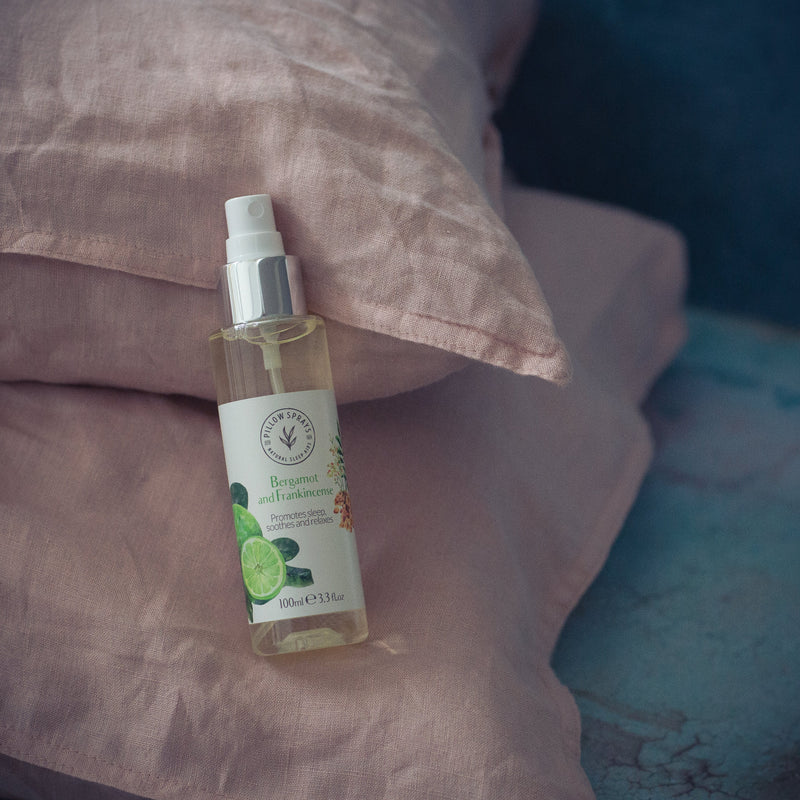 Bergamot and Frankincense Pillow Spray beside bed