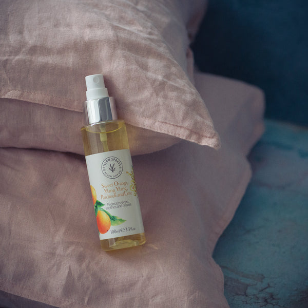 A Sweet Orange, Ylang Ylang, Patchouli and Lime Pillow Spray on a bed