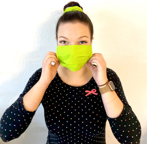 young woman with black shirt with white dots wearing a yellow happy mask easy with white dots