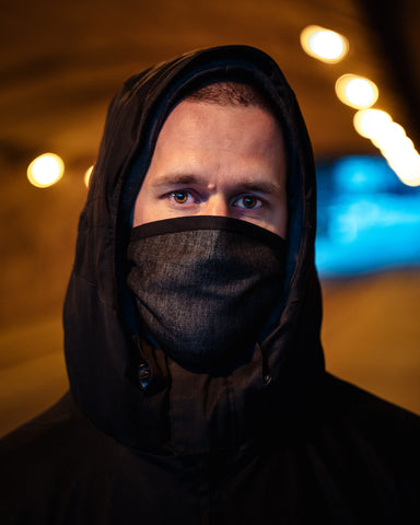 Man wearing windbreaker jacket, hood on his head and dark grey facemask covering his mouth and nose