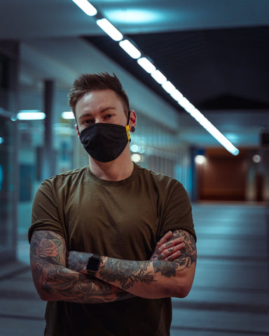 Young man with tattoos wearing a black mask with flowers while crossing his arms in front of his body