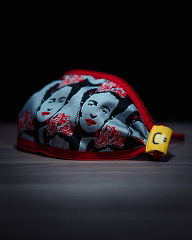 front view on red and blue frida kahlo facemask laying on a wooden board in front of a jet black background
