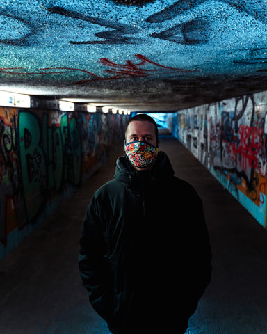 Man wearing power flower face mask standing in a tunnel covered in graffiti
