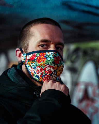 Young man wearing colourful power flower face mask with his hand on his chin