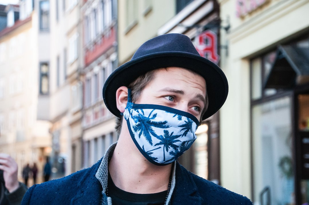 Millennial male wearing a hat and face mask with blue palms on it