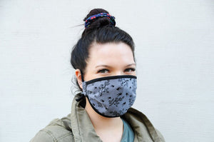 Millennial girl wearing a grey face mask with black birds and tree branches on it