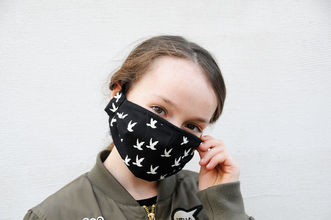 Young girl wearing a black cotton respirator with white flying doves on it