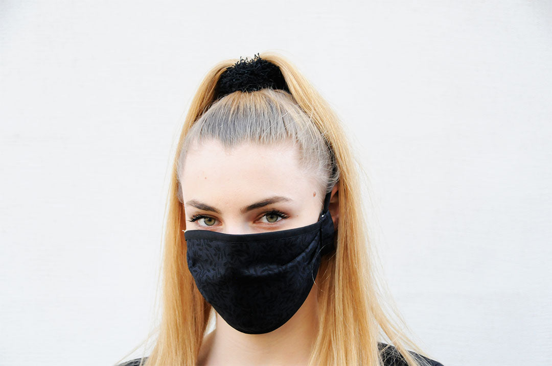 Blonde woman wearing a black face mask with a flower pattern