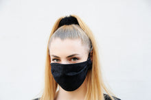 Load image into Gallery viewer, Blonde woman wearing a black face mask with a flower pattern