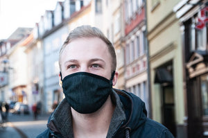 blonde male standing in front of houses wearing dark grey respirator
