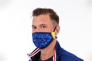 man is wearing blue reusable face mask with flowers birds and rabbits