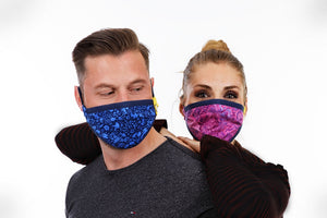 Young couple is wearing reusable face masks in different colors. Man with blue mask and girl with pink mask