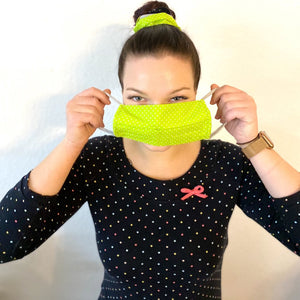 young woman with black shirt with white dots putting on a yellow happy mask easy with white dots