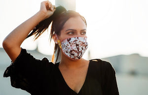 young brown haired woman wearing a reusable face mask featuring a colourful paint stain design