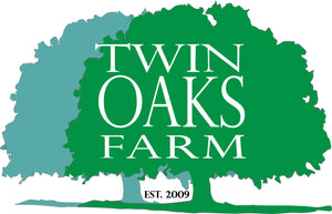 Two oak trees are overlapped in two different shades of green with the words Twin Oaks Farm, Est. 2009 written over them
