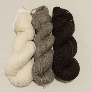 Three skeins of DK weight yarn, cream, medium grey and dark grey