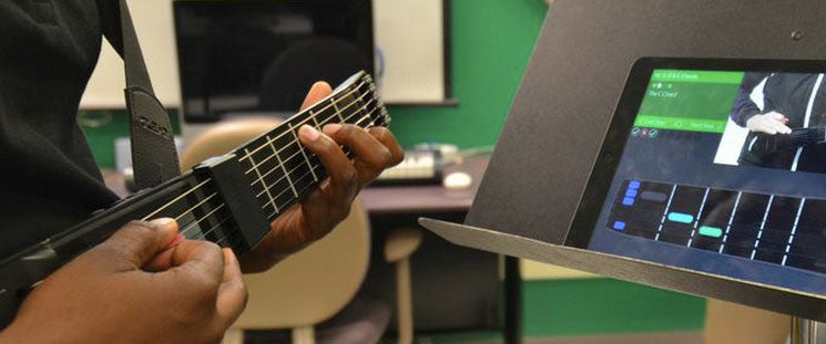 "A student learning a ""C"" chord with the jamTutor app"
