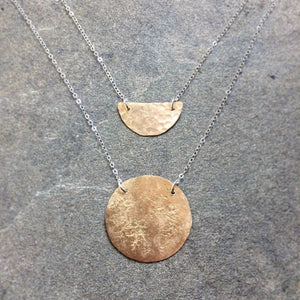 Solid brass moon and small pebbled brass moon, both floating on sterling silver chain.