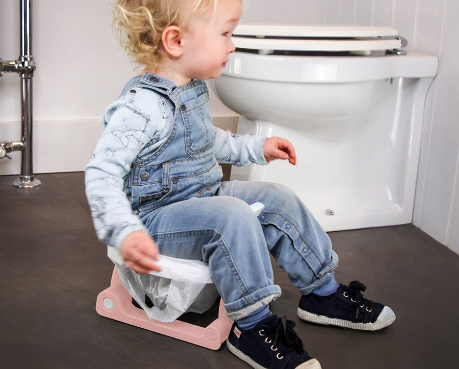 Child sitting on portable travel potty