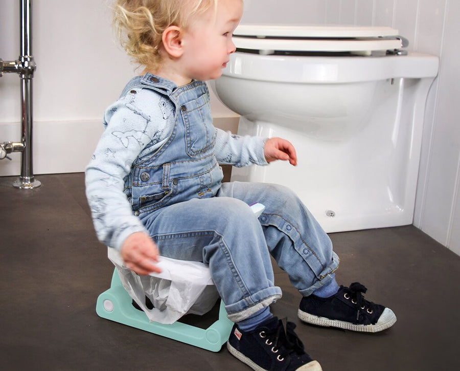 Child sitting on portable potty