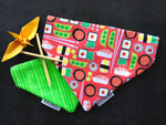 An over the collar reversible dog bandana with sushi, edamame, and chopsticks on a coral background on one side, and two shades of vertical green stripes on the other side.
