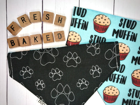 Over the collar reversible dog bandana with white paw prints on a black background on one side, and muffins and printed 'stud muffin' on a mint background on the other side