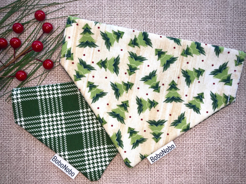 Reversible dog bandana that is forest green and cream plaid on one side and cream with rustic evergreen trees and red polka dots on the other side
