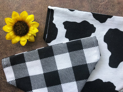 Reversible over the collar dog bandana with white and black cow print on the front, and a black white plaid pattern on the back.