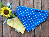 An over the collar reversible dog bandana that is bright blue with medium white polka dots on one side, and white daisies on the other side on a yellow background.