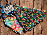 Reversible dog bandana that says happy birthday in rainbow colors on a black background on one side, and rainbow plaid with a white background on the other side