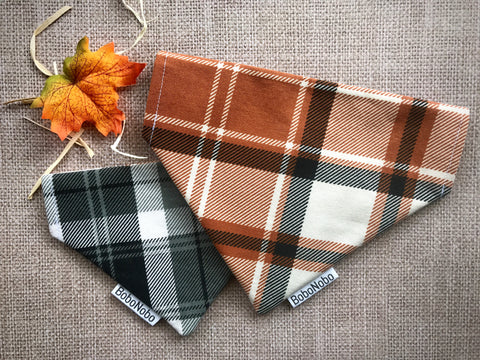 Reversible dog bandana with brown, black, white plaid print on one side and black, gray, and white plaid print on the reverse
