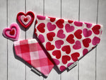 Over the collar reversible dog bandana with hot pink and red hearts on a white background on one side and a matching plaid of white, red, and pink checkered print on the reverse